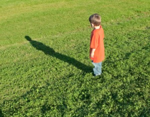young boy looking at his elongated shadow on the grass